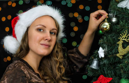 decorates: Attractive woman decorates the Christmas tree