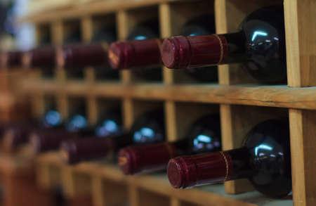 木製ラック上に積層された赤ワインのボトル 写真素材