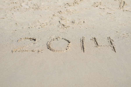 2014 escrito en la playa de arena. photo