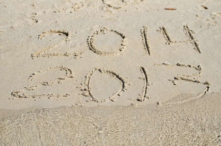 2013 replace 2014. Written on sand beach. photo