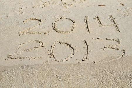 zastąpić: 2013 replace 2014. Written on sand beach.