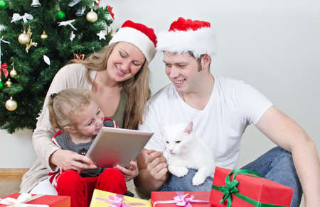 Family with tablet pc in front of christmas tree  photo