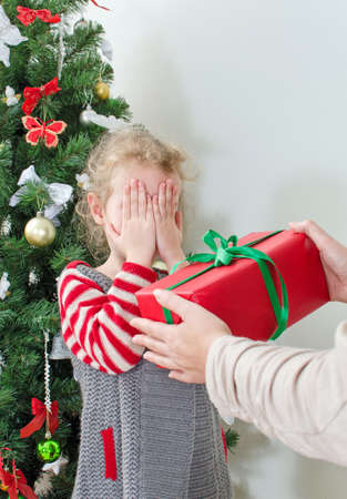 Woman surprising little girl with christmas gift photo