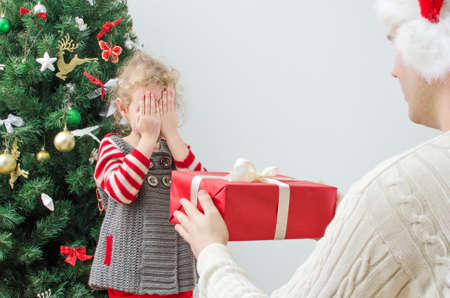 Father surprising little girl with christmas gift photo