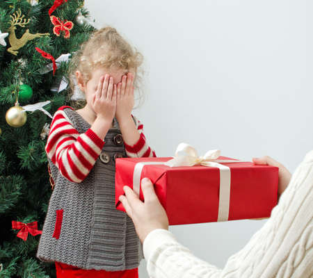 Man surprising little girl with christmas gift photo