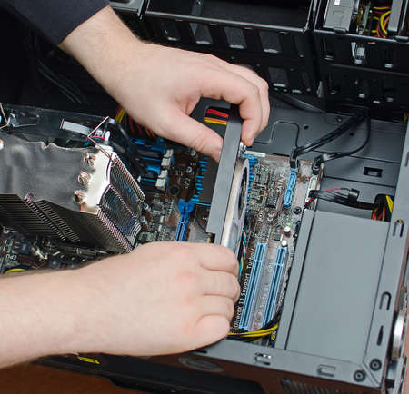 Hands of technician installing graphic card