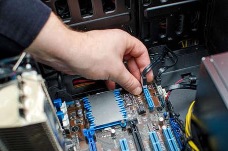 Hands of technician installing HDD on motherboard 免版税图像