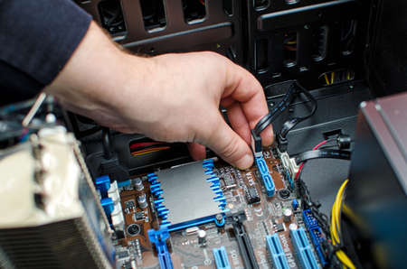ordinateur bureau: Mains de technicien de l'installation du disque dur sur la carte m�re Banque d'images