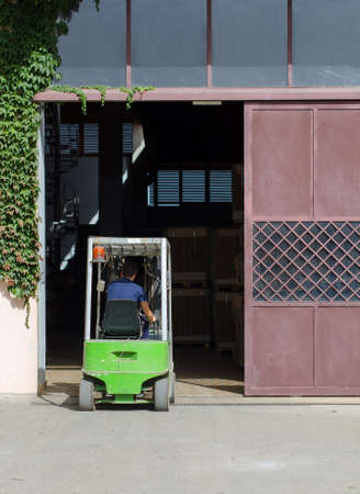 Warehouse worker loading boxes by forklift photo