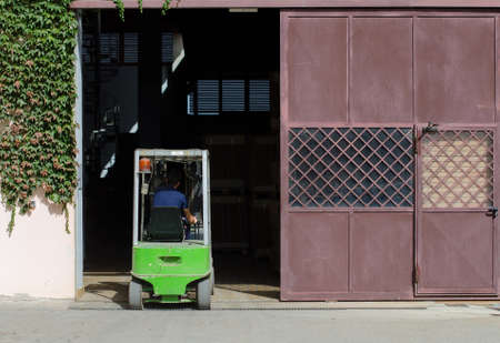 stockpiling: Warehouse worker loading boxes by forklift