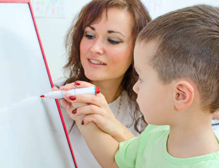 Little boy with teacher near whiteboard photo