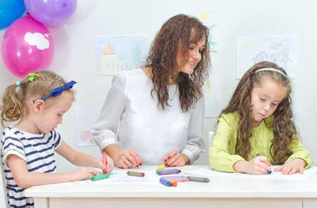 Teacher with two girls in kindergarten
