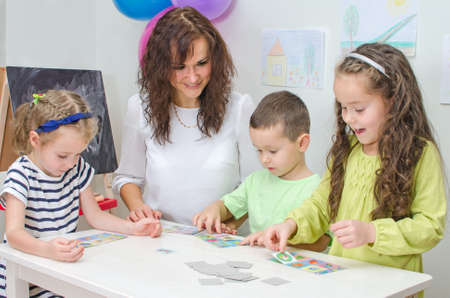 Teacher plays with children in kindergarten  photo