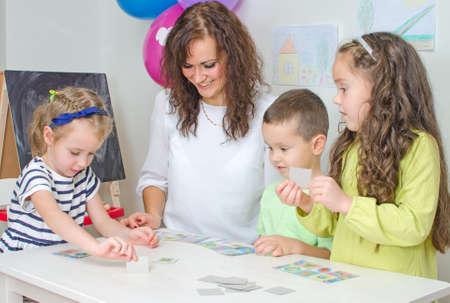Teacher plays with children in kindergarten