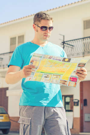 Young handsome man travel with a map in the town