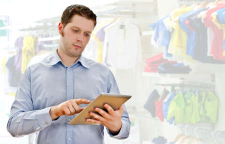 Supervisor with tablet pc in the clothing store photo