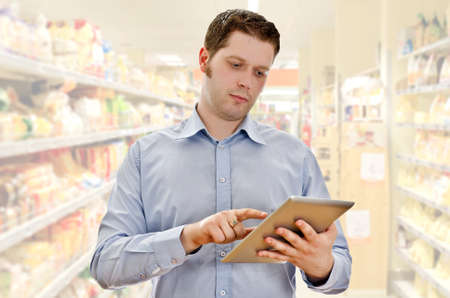 Supervisor with tablet pc in the grocery store photo