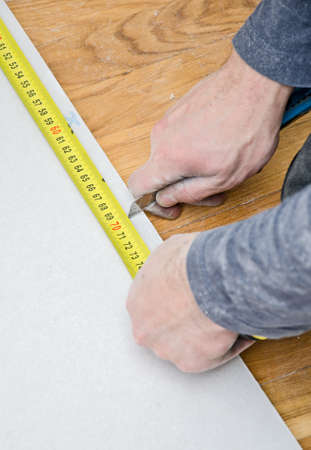 Male hands measuring and cutting gypsum plasterboard photo