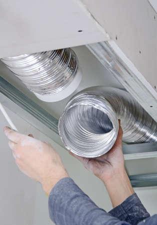 Mannelijke handen opzetten ventilatiesysteem binnenshuis Stockfoto