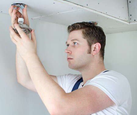 Certified electrician installing light bulb photo