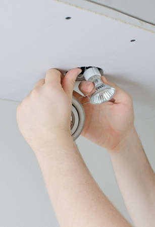 Male hands installing light bulb photo