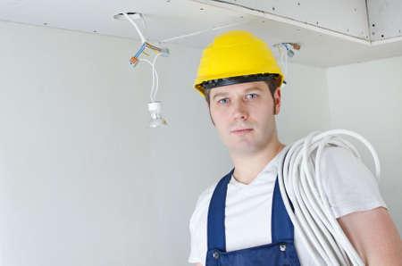 journeyman technician: Certified electrician worker in yellow hardhat