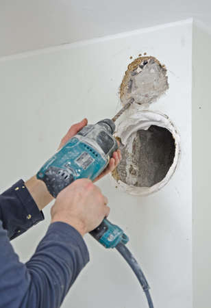 Man with jackhammer doing hole for ventilation photo