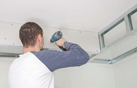Builder mounting gypsum plasterboard frame on the wall 免版税图像