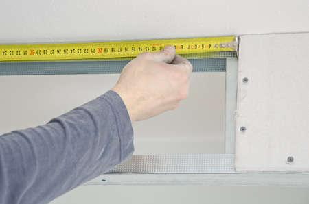 Male hands measuring gypsum plasterboard frame photo