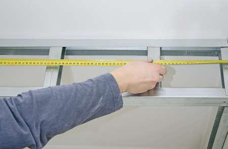 plasterboard: Male hands measuring gypsum plasterboard frame