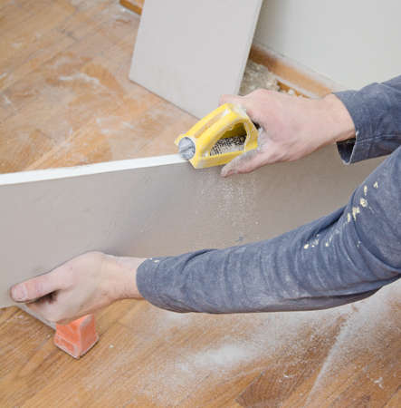 sidewall: Male hand grinding gypsum for smoothing surface