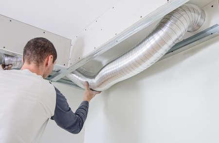 Man opzetten ventilatiesysteem binnenshuis Stockfoto