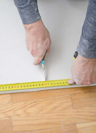 plasterboard: Male hands measuring and cutting gypsum plasterboard