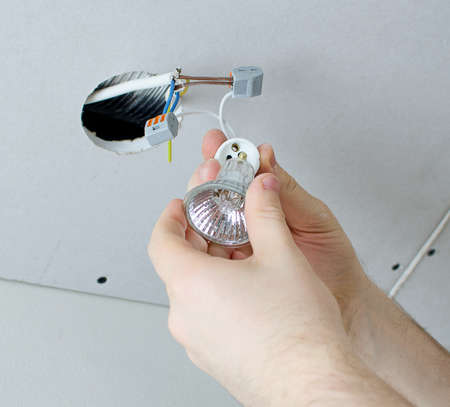 electrical contractor: Male hands installing socket for light bulb Stock Photo