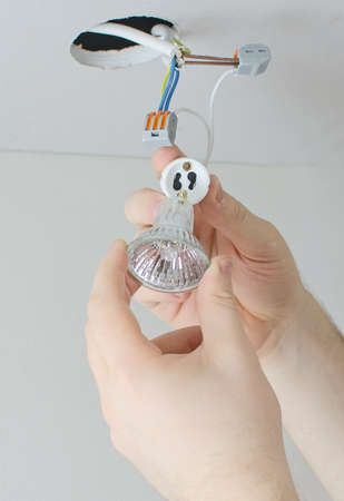 Male hands installing socket for light bulb photo