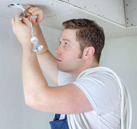 認定電気技師は電球のソケットをインストールします。