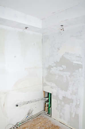 undone: Room renovation. Gypsum plasterboard with undone socket bulbs.
