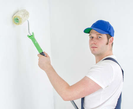 Painter in uniform paints the wall. photo