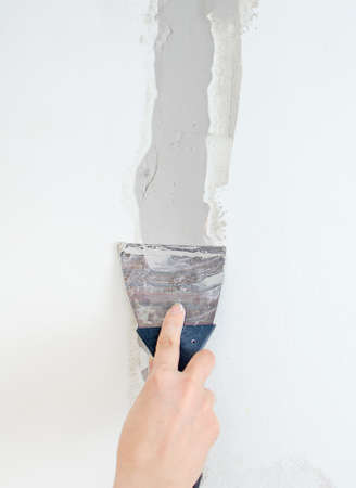 Vrouwelijke hand reparaties muur met spackling pasta