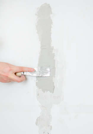 patching: Female hand repairs wall with spackling paste