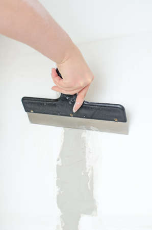 putty knives: Female hand repairs wall with spackling paste