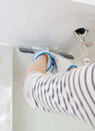 putty knives: Hand repairs gypsum plasterboard frame with spackling paste