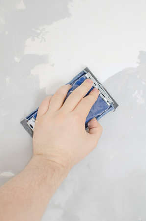 Males hand grinding wall with sandpaper. photo