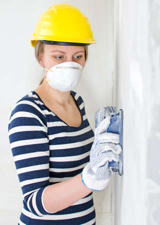 Female plasterer in hard hat polishing the wall. photo