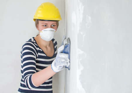 sidewall: Female plasterer in hard hat polishing the wall. Place for your text.
