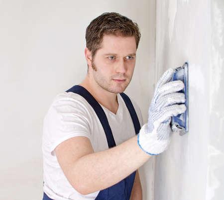 Male plasterer in uniform polishing the wall. Stock Photo