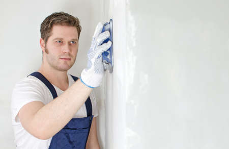 priming paint: Male plasterer polishing the wall. Space for text.