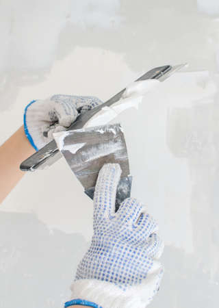 Hands working with spackling paste