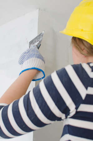 patching: Female plasterer repairs wall with spackling paste