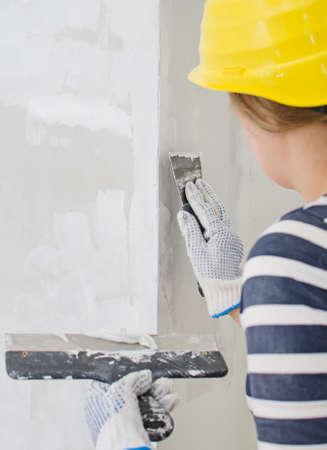 女性左官修理壁パテ貼り付け 写真素材